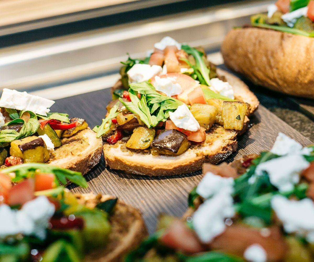 Nahaufnahme belegter Brote mit Gemüse und Weichkäse